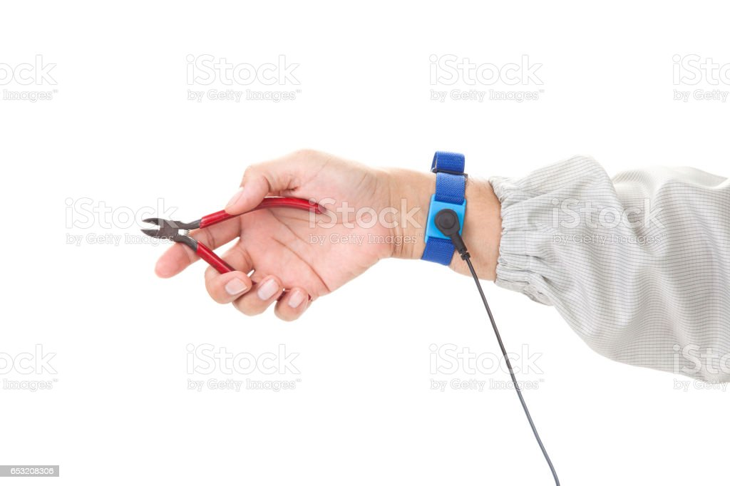 Bracelet on the hand of a man wearing ESD cloth holding a wire cutters, static resistance (ESD) bracelet or ground equipment, anti-static, used to safely ground is working. electronic devices stock photo