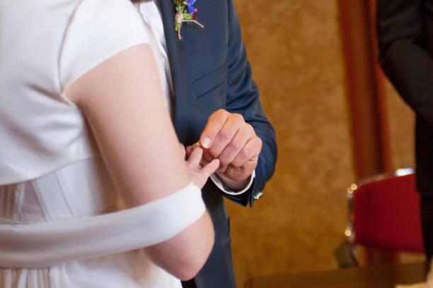 Braeutigam steckt Braut den Ring an den Finger – Foto