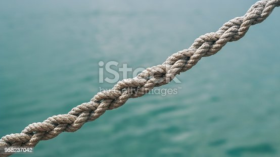 Closeup shot of a braided rope with a blurred water background