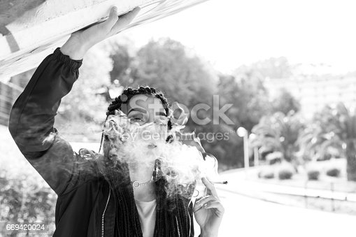 istock Braided young woman smoking outdoors. 669420024