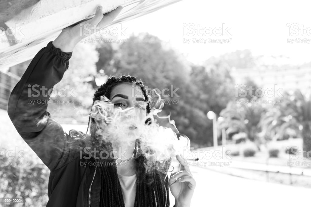 Braided young woman smoking outdoors. stock photo