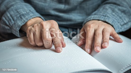 istock Braille book for low vision/ blind person reading Braille sign by finger touching embossed texture paper for World sight day and World Braille day awareness concept 1017945546