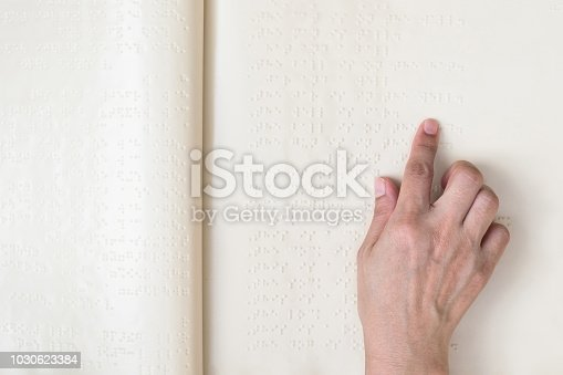 1017945546 istock photo Braille book for low vision/ blind person reading Braille sign by finger touching embossed texture paper for World sight day and World Braille day awareness concept 1030623384