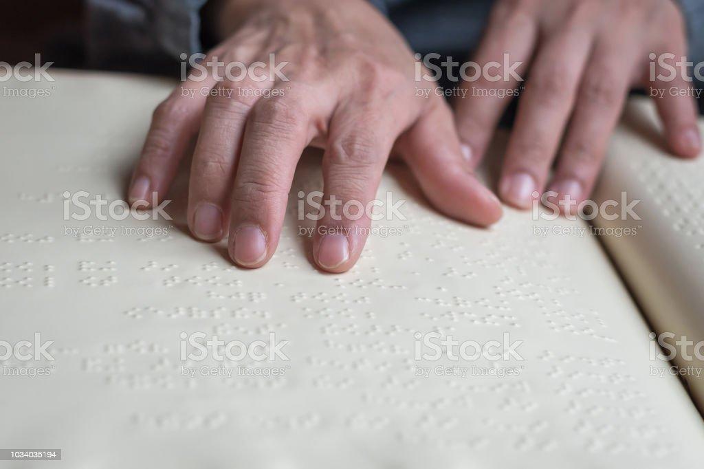 弱視の点字本盲人に指が触れるこ...