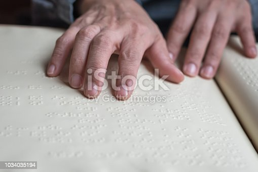 1017945546 istock photo Braille book for low vision/ blind person reading Braille sign by finger touching embossed texture paper for World sight day and World Braille day awareness concept 1034035194