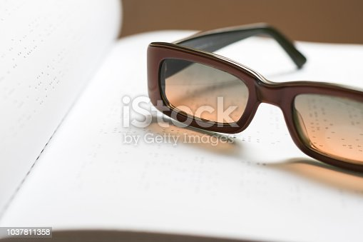 1017945546 istock photo Braille book for low vision/ blind person reading Braille sign by finger touching embossed texture paper for World sight day and World Braille day awareness concept 1037811358