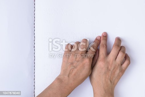 1017945546 istock photo Braille book for low vision/ blind person reading Braille sign by finger touching embossed texture paper for World sight day and World Braille day awareness concept 1047876040