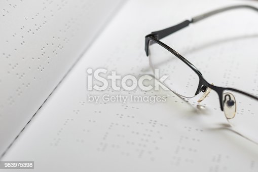 1017945546 istock photo Braille book for low vision/ blind person reading Braille sign by finger touching embossed texture paper for World sight day and World Braille day awareness concept 983975398