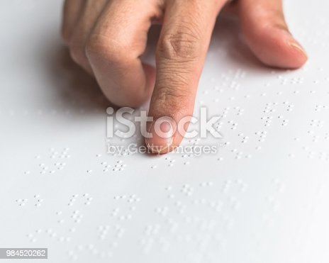 1017945546 istock photo Braille book for low vision/ blind person reading Braille sign by finger touching embossed texture paper for World sight day and World Braille day awareness concept 984520262