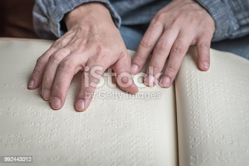 1017945546 istock photo Braille book for low vision/ blind person reading Braille sign by finger touching embossed texture paper for World sight day and World Braille day awareness concept 992443012