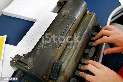 hands typing on a braille typing machine. Braille is a tactile writing system used by people who are blind traditionally written with embossed paper