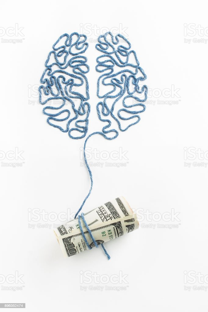 Brain and money connected by a thread on a white background stock photo