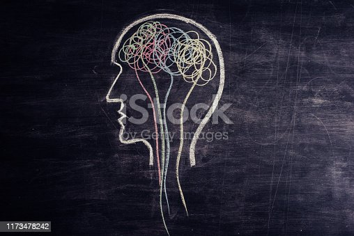 Human brain maid of multicoloured chaotic lines drawn on a blackboard. There are straight lines going down the spine.