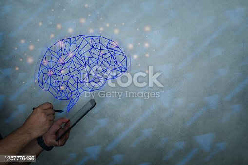 istock Brain representing artificial intelligence and businessman holding futuristic tablet. Data mining and another modern computer technologies concepts. 1257776496