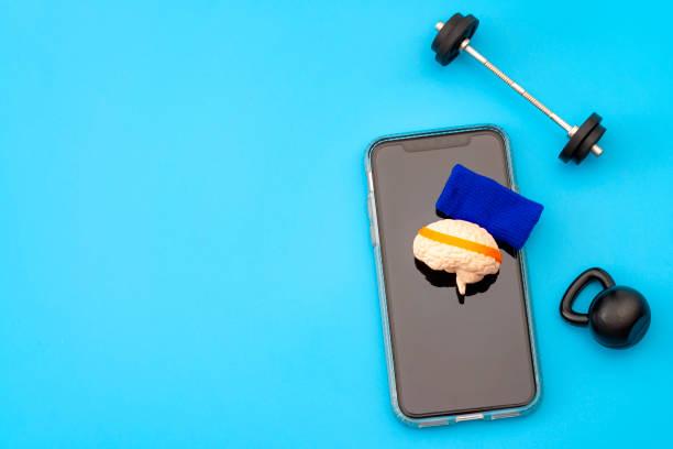 Entrenamiento cerebral, aplicación de mejora de neurología y concepto de entrenamiento mental con cerebro humano con banda de sudor, cencerro y pesas libres y teléfono inteligente aislado en fondo azul con espacio de copia - foto de stock