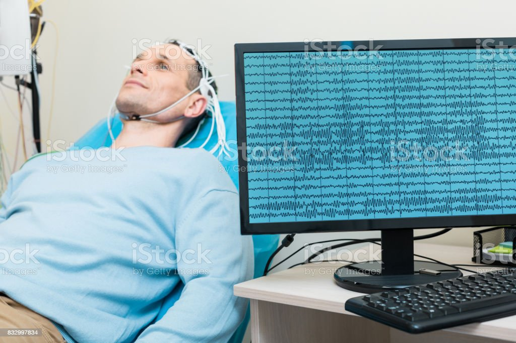 Brain waves of young man being displayed on screen stock photo