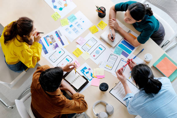 Brainstorm planing creative asian teamwork,  Group of asia mobile phone app developer team meeting for share ideas about screen display prototype layout for smartphone, ui, ux startup small business, top view stock photo