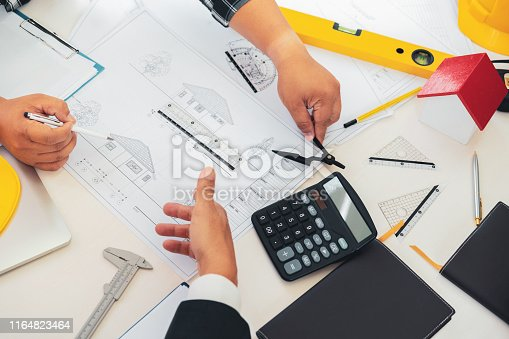 832105172 istock photo Brainstorming architects teamwork discussing about construction plans on blueprint at construction site office. 1164823464