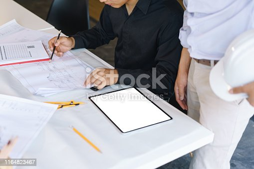 912867216istockphoto Brainstorming Architects teamwork discussing,designing and sketching the building construction project. 1164823467
