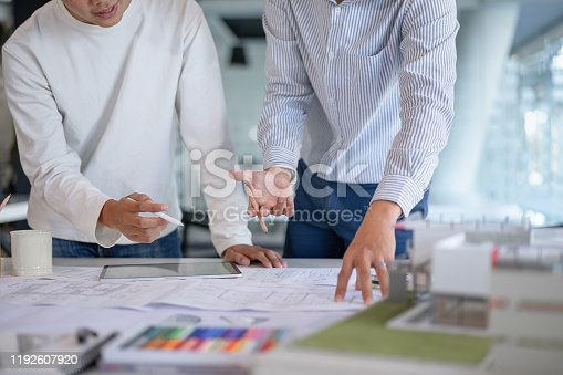976560476 istock photo Brainstorming Architects teamwork discussing,designing and sketching the building construction project. 1192607920