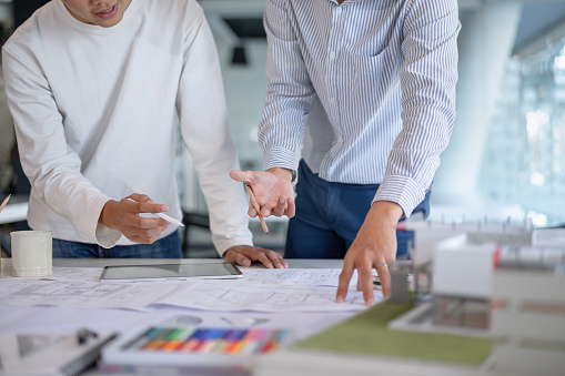 912867216 istock photo Brainstorming Architects teamwork discussing,designing and sketching the building construction project. 1192607920