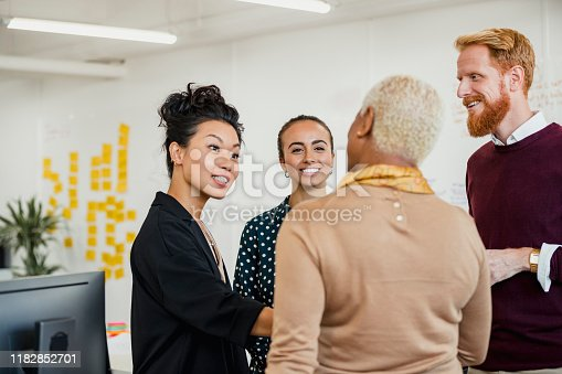 Colleagues standing in a small group discussing something while working at an office.
