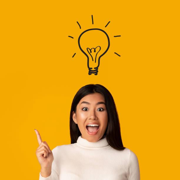 koncepcja burzy mózgów. pomysł lampa świecąca nad głową dziewczyny - natchnienie zdjęcia i obrazy z banku zdjęć