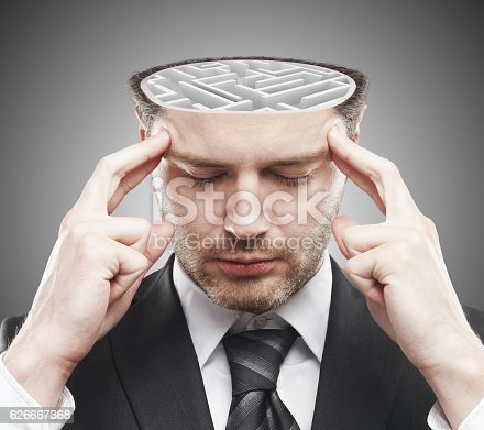 Thoughtful young businessman with abstract concrete maze inside head. Brainstorming concept