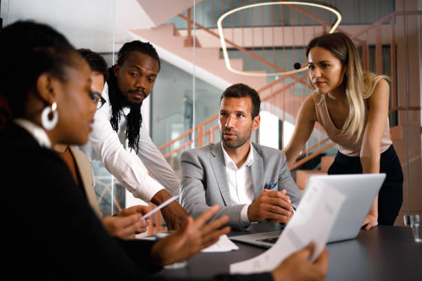 Brainstorming A diverse group of businesspeople is having a meeting in the office. They sit and stand around a table in the modern office and try to find the best ideas. georgijevic coworking stock pictures, royalty-free photos & images