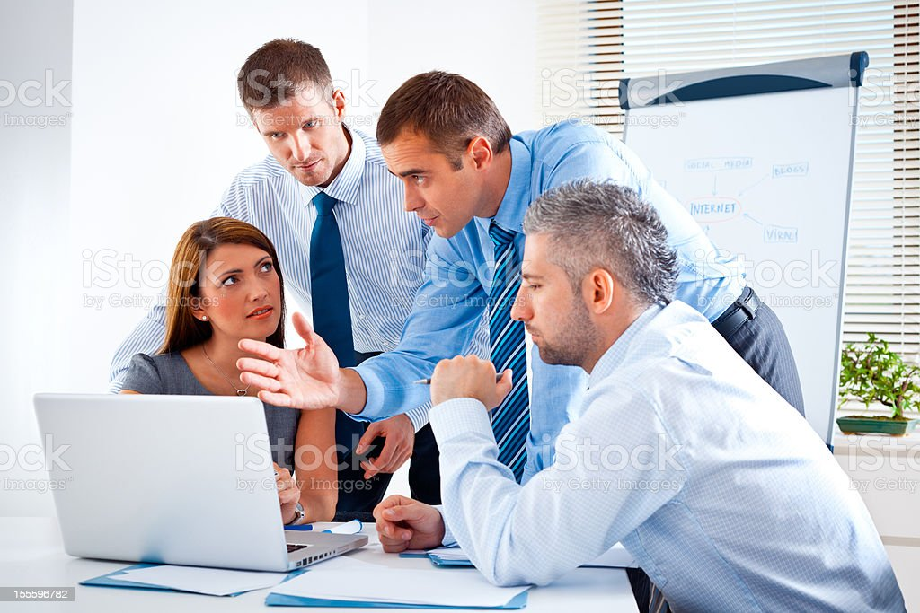 Brainstorming Businness team discussing a strategy of their company in a board room. Adult Stock Photo
