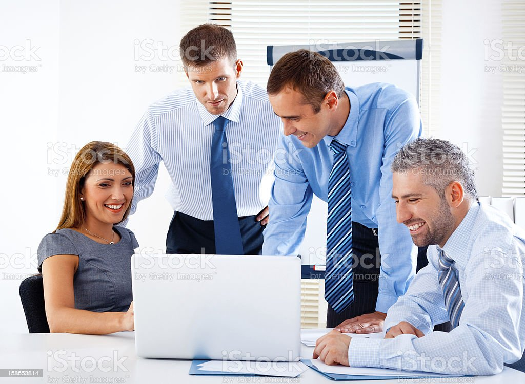 Brainstorming Four heppy business people having meeting in a board room and discussing strategy of their company. Adult Stock Photo