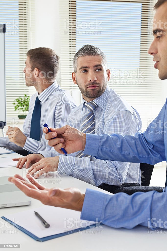 Brainstorming Three businessmen discussing in the meeting room. A Helping Hand Stock Photo