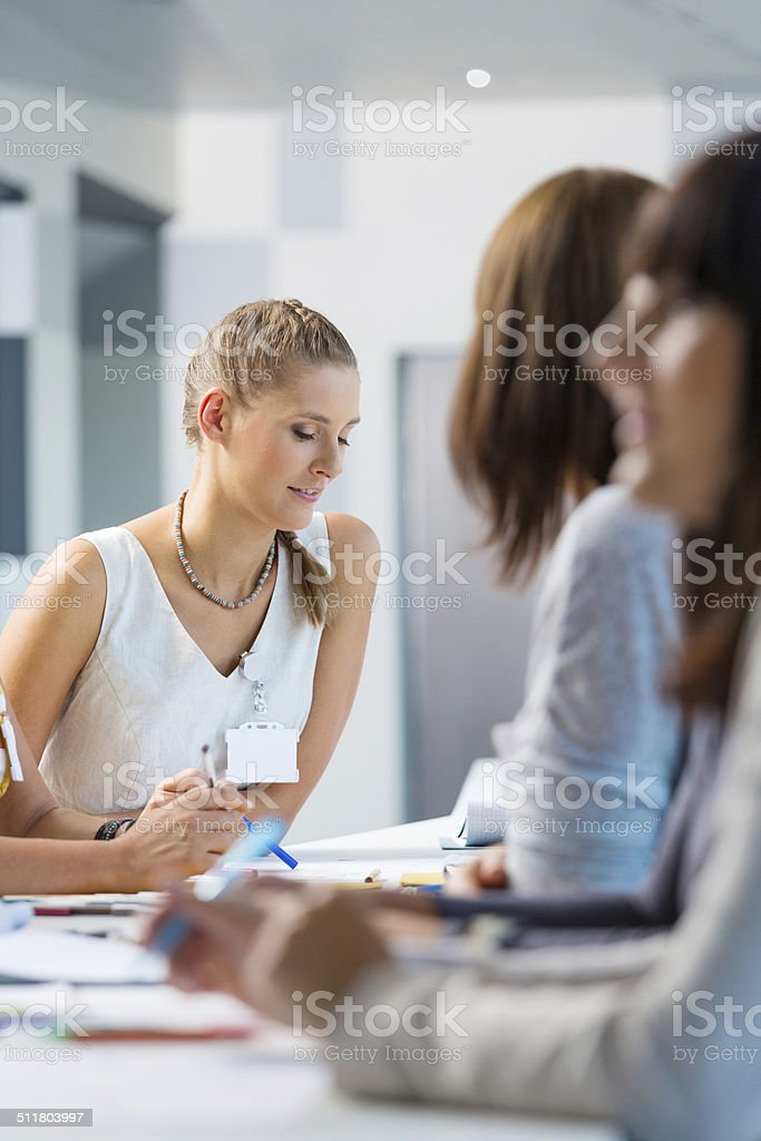 Brainstorming Group of women sitting at the conference table and disccusing a project. Focus on blonde. Adult Stock Photo