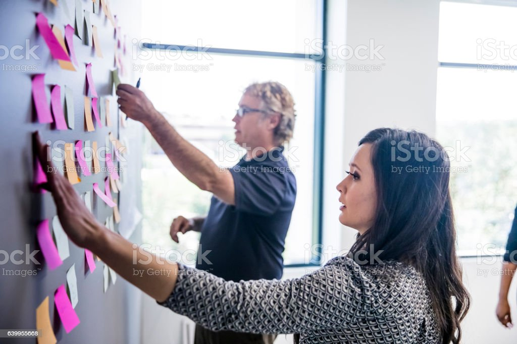 Brainstorming with Notes on the Wall An attractive young Asian businesswoman and a mature man leading a brainstorming session by putting post it notes on the wall Adhesive Note Stock Photo