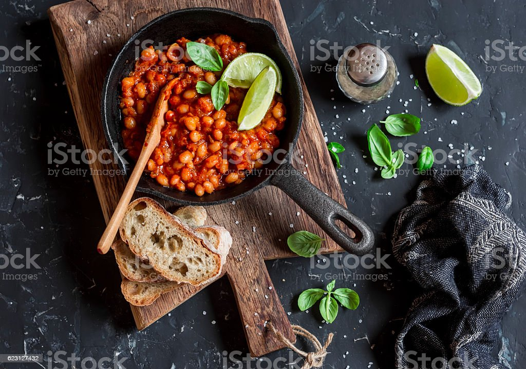 Braised beans in tomato sauce in a cast iron pan - foto de acervo