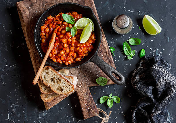 Braised beans in tomato sauce in a cast iron pan stock photo