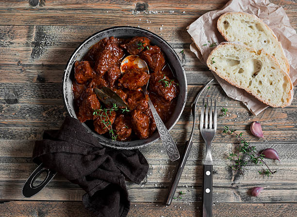Braised beef in a frying pan on a wooden rustic table. Braised beef in a frying pan on a wooden rustic table. Top view beef stew stock pictures, royalty-free photos & images
