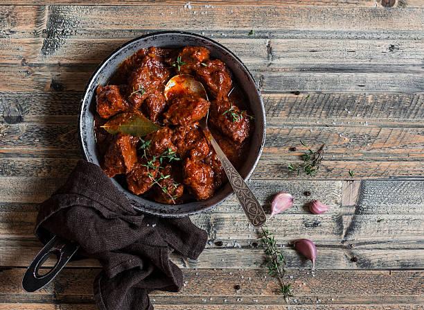 braised beef in a frying pan on a wooden table - weinsoße stock-fotos und bilder