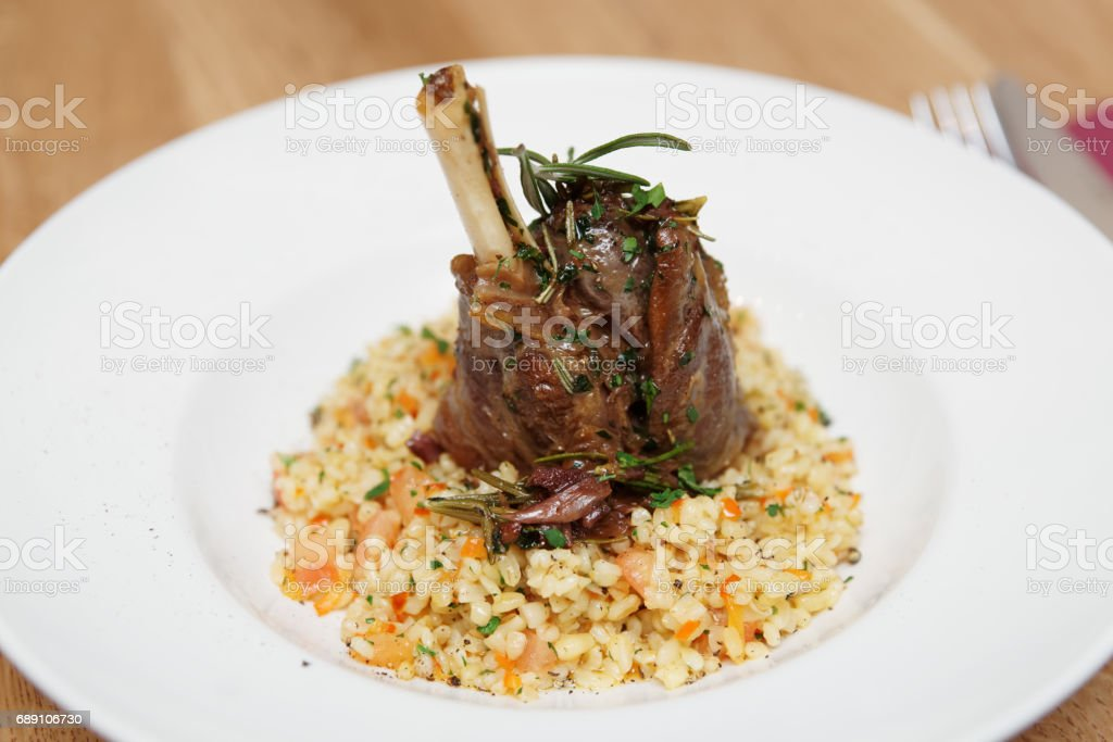 Braised lamb shank with bulgur stock photo