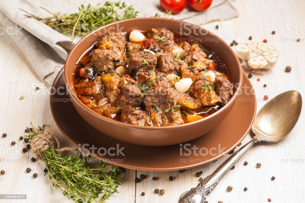 Braised meat with vegetables in a thick sauce. A large portion in a deep plate is ready to eat. Rustic decoration on a dark wooden background. Braised meat with vegetables in a thick sauce. A large portion in a deep plate is ready to eat. Rustic decoration on a light wooden background. Close up. American Culture Stock Photo