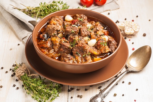 Braised Meat With Vegetables In A Thick Sauce A Large Portion In A Deep Plate Is Ready To Eat Rustic Decoration On A Dark Wooden Background Stock Photo - Download Image Now