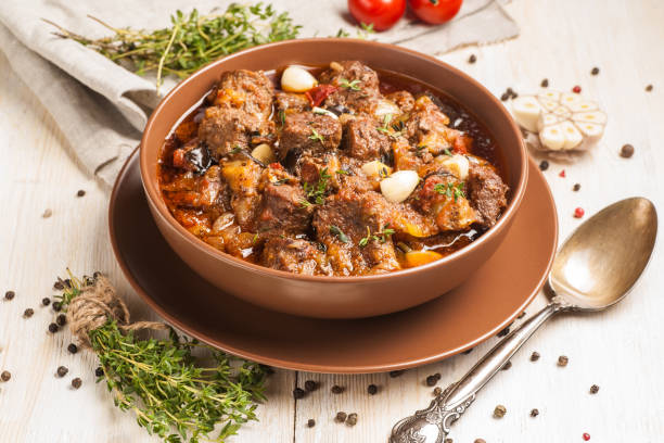 Braised meat with vegetables in a thick sauce. A large portion in a deep plate is ready to eat. Rustic decoration on a dark wooden background. Braised meat with vegetables in a thick sauce. A large portion in a deep plate is ready to eat. Rustic decoration on a light wooden background. Close up. ragout stock pictures, royalty-free photos & images