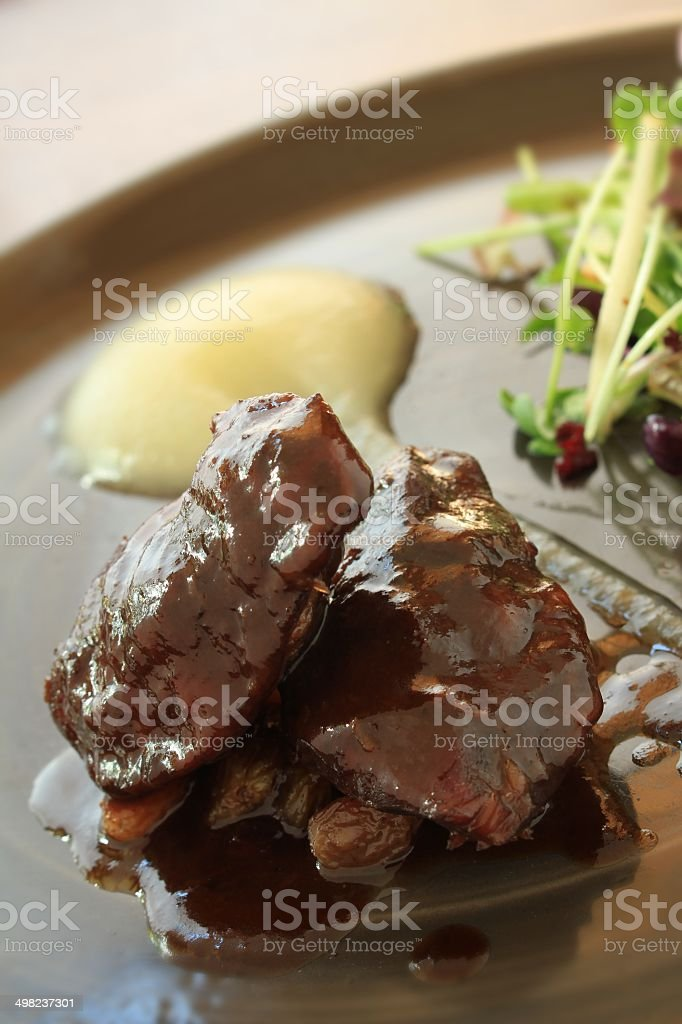 braised pig cheeks plated meal stock photo
