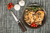 Stewed pork chop in a bright mushroom sauce. Top view.