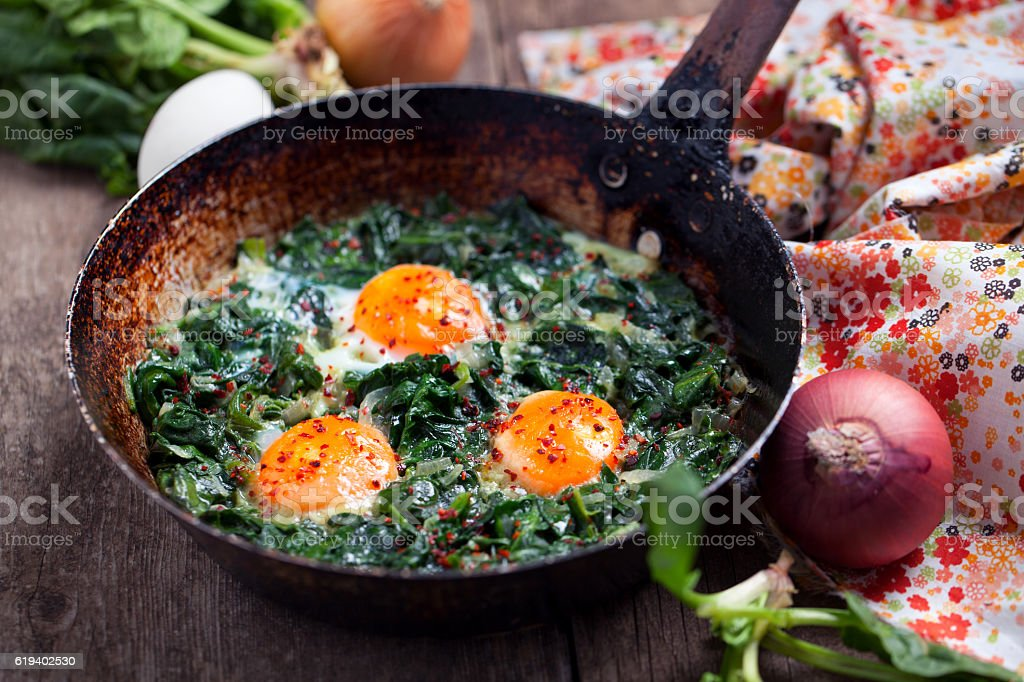Braised spinach and eggs in an old frying pan stock photo