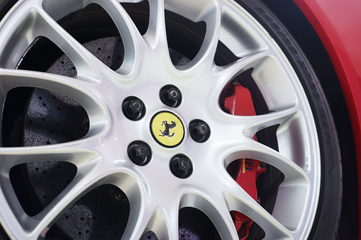 Maranello, Italy - April 27, 2015: Close-up of brake disc and alloy rim of an  Ferrari whit logo in center. The logo of a Ferrari was designed by Pininfarina.