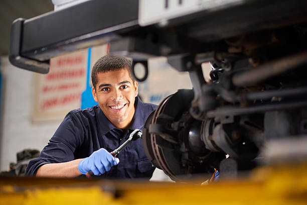 Brake discs A young mechanic is smiling to camera as he works on a car in a garage repair shop. He is wearing blue overalls.  He is fixing the brake discs on the front driver's side of the vehicle. auto mechanic stock pictures, royalty-free photos & images
