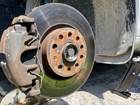 Image of a brake rotor on a car after the tires has been removed, used and rusty.