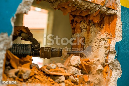 Construction worker braking the wall with machine