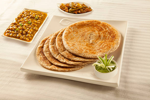 Bran paratha puri served with chickpeas cholay and pickle chutne Bran paratha puri served with chickpeas cholay and pickle chutney dal makhani stock pictures, royalty-free photos & images
